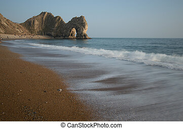 Beach at Durdle Door, Dorset with the waves lapping the...