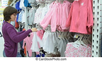 Woman shopping in the section of children clothes - Young...