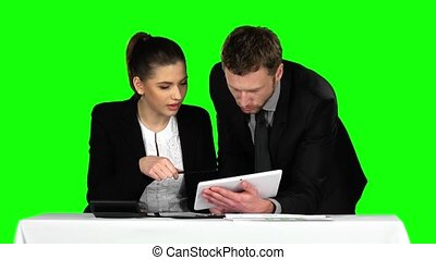 Business man and woman using laptop in office lobby. Green screen