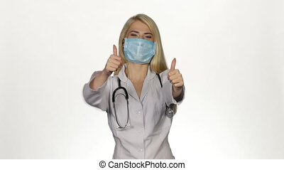 Female doctor making thumbs up sign. - Professional doctor...