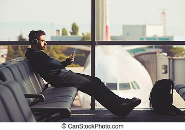 Travel at the airport - Young traveler is waiting at the...