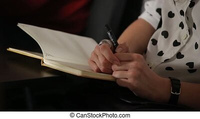 Woman holding a pen and notebook at a seminar event Close-up...
