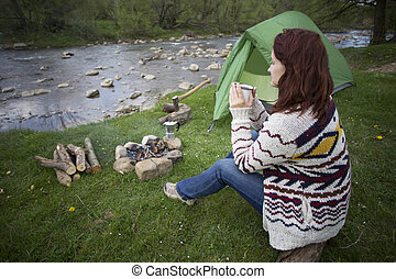 Girl sitting near a campfire - A girl sits by the fire and...