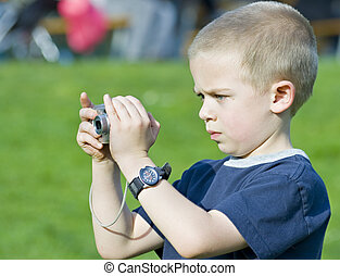 Candid close up portrait of a cute six year old boy taking a photograph