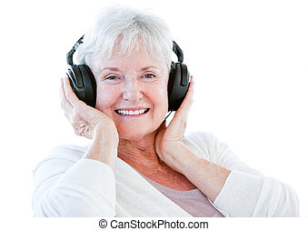 Smiling senior woman listening music with headphones against...