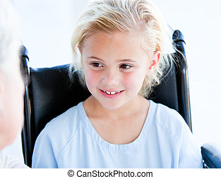 Blond little girl sitting on a wheelchair in a hospital