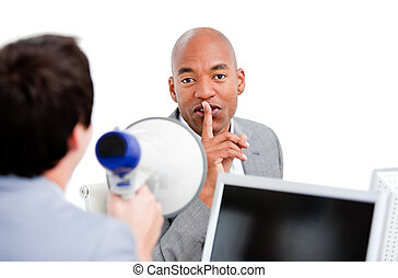 Afro-american businessman asking for silece while his colleague yelling through a megaphone in the office