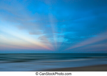 Seascape with sun beams at sunset
