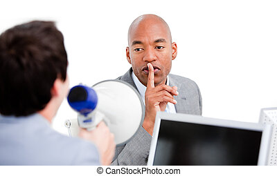 Confident businessman asking for silece while his colleague yelling through a megaphone in the office