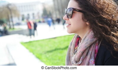 happy young woman in glasses sits on a bench in the city