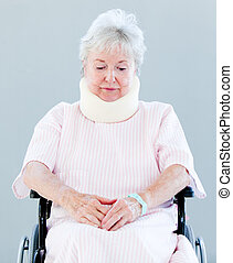 Upset senior woman with a neck brace sitting on a wheelchair...