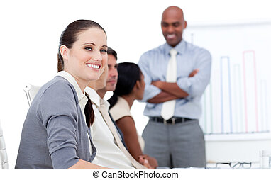 Smiling businesswoman looking at the camera during a meeting with her team in a company