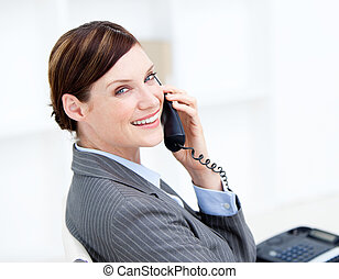 Confident businesswoman on phone sitting at her desk