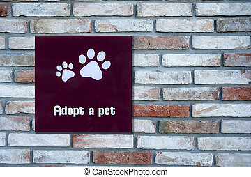 Adopt a pet sign on brick wall
