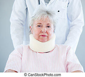 Portrait of a senior woman with a neck brace sitting on a wheelchair in a hospital