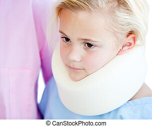 Close-up of a little girl with a neck brace in a hospital