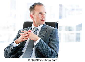 Confident businessman thinking about the company in the...