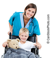 Nice female doctor carrying adorable little boy in the wheelchair at the hospital