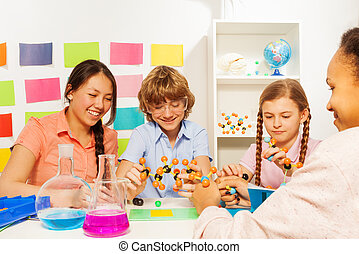 Four students studying chemistry at the classroom - Four...
