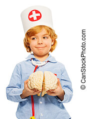 Cute boy playing doctor with toy human cerebrum