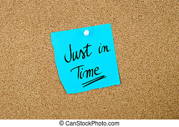 Just In Time written on blue paper note pinned on cork board...
