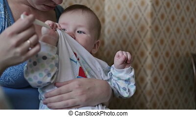 Mum feeds the child - Baby sits at a children's little...