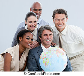 Multi-ethnic businessteam holding a globe in the office of...