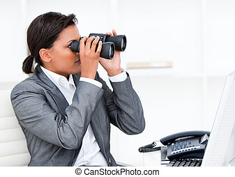 Self-assured businesswoman looking through binoculars in the...