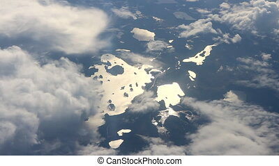 Beautiful view under wing. Shining sun lake, islands,...