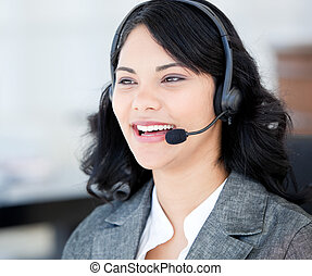 Joyful businesswoman wearing a headset to talk with customer...