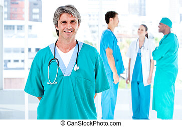 Joyful male doctor looking at the camera while his medical...