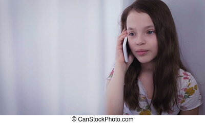 Beautiful happy little girl emotional talking on smartphone...