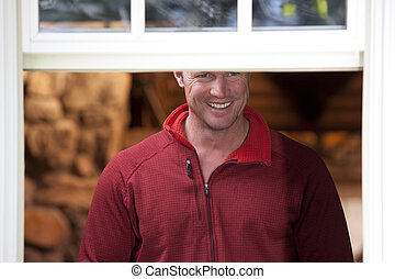 Man Smiling and Looking Out A Window - A man wearing a red...