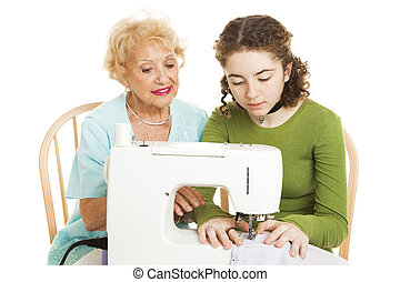 Family Sewing Lesson - Senior woman teaching her teenage...