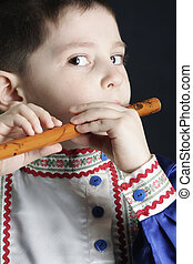 Little boy playing wooden flute - Little boy in blue playing...