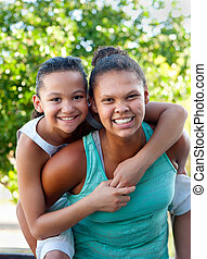 Two happy young gilrs - An older teenage girl carries a...