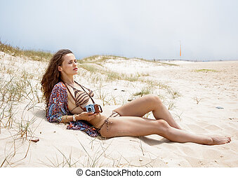Relaxed bohemian woman with retro photo camera laying on...