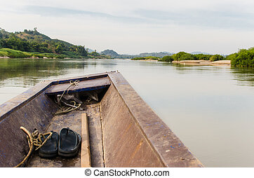 Wooden longtail boat heads out into the Mekong River,...