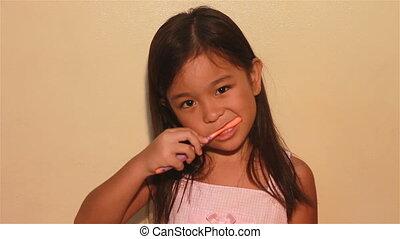 kid brushing her teeth