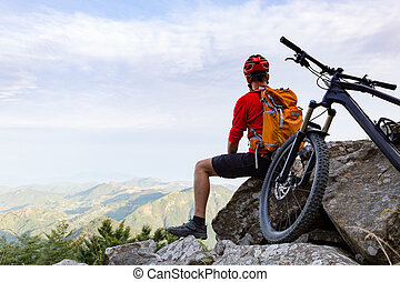 Mountain biker looking at view on bike trail in autumn...