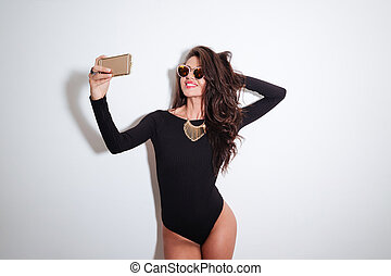 Smiling woman in bodysuit making selfie photo on smartphone...