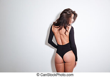 Back view portrait of a sexy woman standing isolated on a...