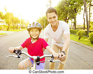 happy little girl with father practice to riding  bicycle