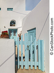 White house blue gate - Image of a traditional white house...