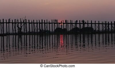 MYANMAR - U Bein Bridge at sunset with people crossing...