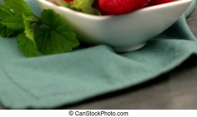 Appetizing strawberry in the bowl on a black slate table top...