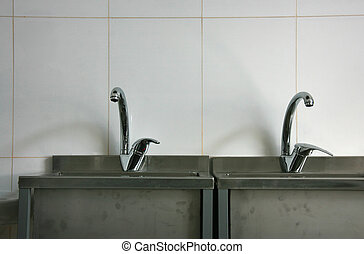 Taps - A photo of taps connected to two stainless steel...