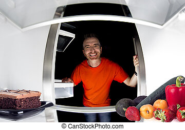 Choosing Between Cake of Fruits - Hungry man looking in the...