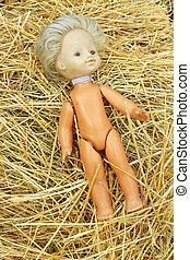 doll lost on the hay - old abandoned doll lays on the hay