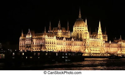 Parliament in Budapest at night while walking on a boat on...